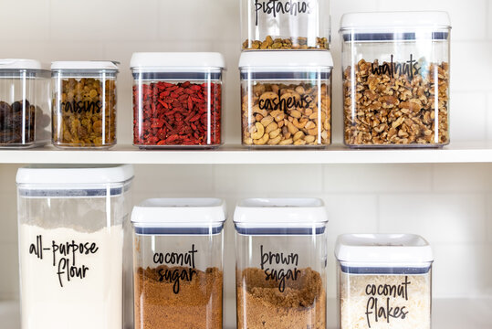 Baking ingredients in BPA-free plastic storage containers with labels in an organized kitchen pantry