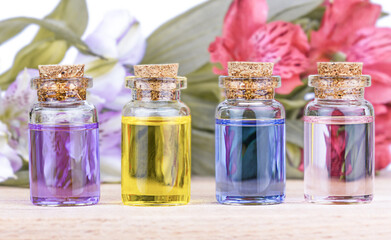 Glass colorful bottles aroma oil and flowers on wooden table.