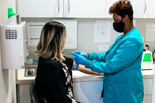 Black nurse draws blood from hispanic woman at medical facility