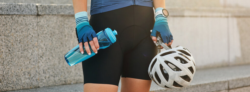 Website header of Cropped shot of young sportive woman holding white bike helmet and water bottle while standing outdoors, getting ready for cycling
