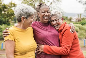 Fototapeta Happy multiracial senior women having fun together outdoor - Elderly generation people hugging each other at park obraz