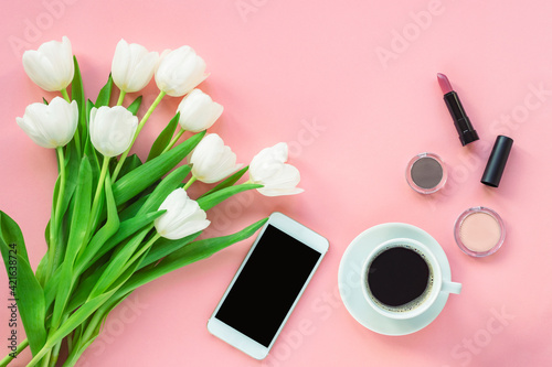 Cup of coffee, phone, cosmetics and bouquet of tulips on pink background, top view. Women's day or Mother's day concept