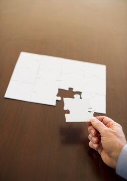 Hand putting last puzzle piece in puzzle