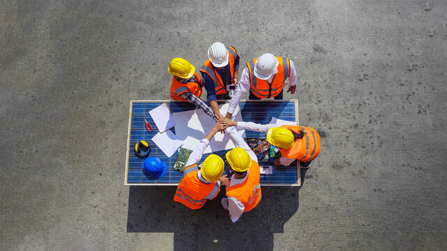 Top view of Architectural engineers putting their hands together on solar panel and his blueprints with Solar photovoltaic equipment on construction site. meeting, discussing, designing, planing