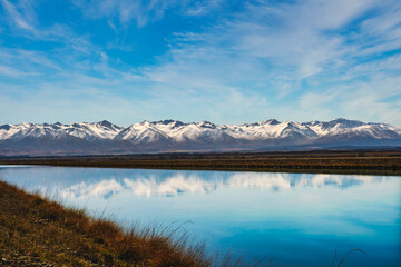 Snow covered Southern Alps mountain range near Twizel reflected in the still water in the canal flowing out of Lake Rautaniwha under some wispy cloud