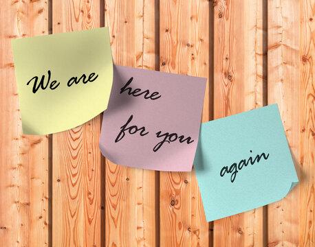 """Haftnotizen mit dem Text """"We are here for you again"""" auf einer Holzwand"""