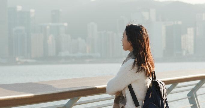 Woman look at the sea at sunset in Hong Kong