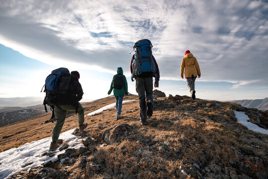 Group of diverse tourists or hikers walks on mountain top