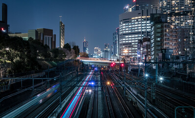 Illuminated Railroad Tracks Amidst Buildings In City At Night