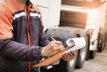 Auto Mechanic Driver holding  Clipboard Checking Maintenance and Safety Program of Semi Truck.
