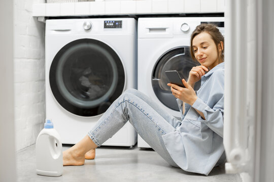 Relaxed woman with a smartphone in the laundry room