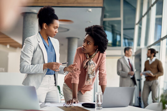 Black business mentor gives instruction to her younger colleague who works on laptop at corporate office.