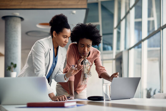 Young black business apprentice talks with her mentor who reviews her work on laptop during meeting in the office.