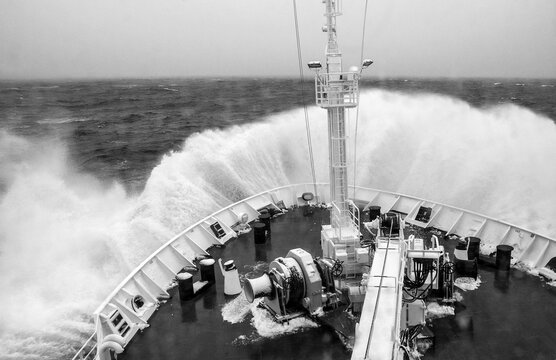 A ships bow see crashing into a stormy head sea