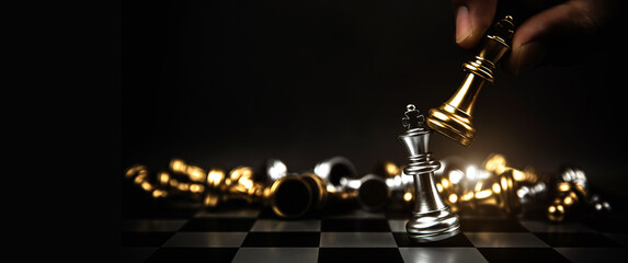 Fototapeta Close up hand choose king chess to challenge battle fighting on chess board concepts of leadership and business strategy and human personal organization risk management. obraz