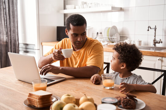 Man drinking tea and chatting with his son while working at the laptop