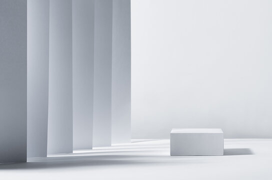 Elegant abstract white podium in sunlight with shadow, striped place with perspective on white background for product display. Simple modern geometric design.