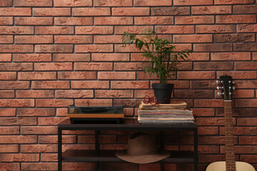 Stylish turntable and vinyl records on shelving unit near red brick wall