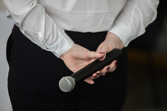 Presenter Giving Presentation and Moving Hand Holding Projector Remote Control. Corporate Business Marketing Manager and Sales Pitch. Speaker in Business Meeting Room Holding Microphone Next to Screen