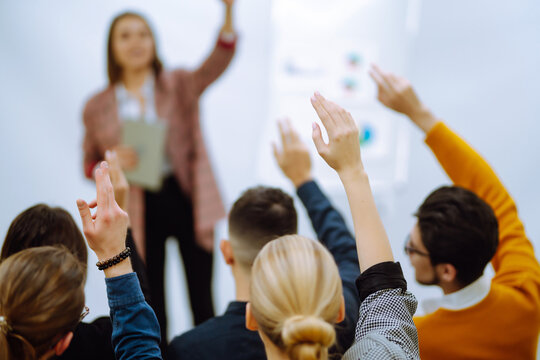 Business people raising hand up to ask question with speaker, to agree or vote for comments in seminar conference. Business group meeting seminar training concept.