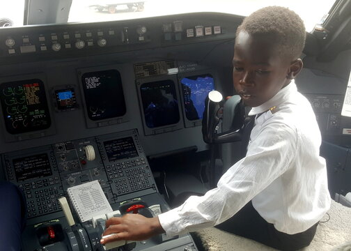 """Ugandan """"Captain"""" Graham Shema, is seen inside the cockpit of a Bombardier CRJ900 aircraft at the Entebbe International Airport, in Entebbe"""