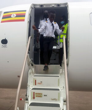 "Ugandan ""Captain"" Graham Shema, and his flight instructor, Simon Wadagu Bruno, disembark from a Bombardier CRJ900 aircraft at the Entebbe International Airport, in Entebbe"