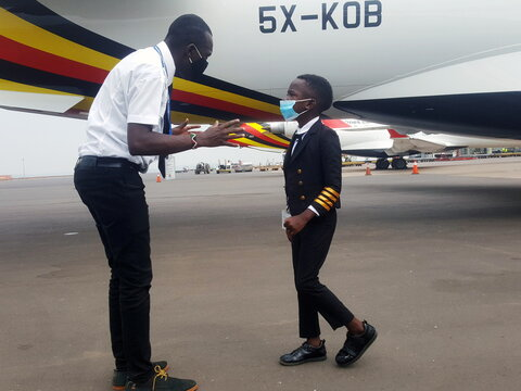 """Ugandan """"Captain"""" Graham Shema, listens to his flight instructor, Simon Wadagu Bruno, about functions of some parts on a Bombardier CRJ900 aircraft at Entebbe International Airport, in Entebbe"""