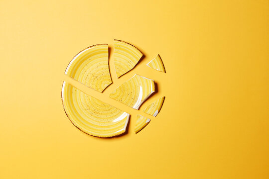 Broken ceramic stylish yellow plate crash with separate large pieces top view isolated on the bright solid yellow fond background