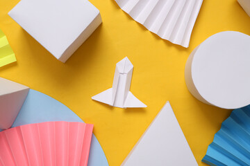 Origami rocket on yellow abstract background with geometric shapes. Minimalism. Concept art. Creative layout