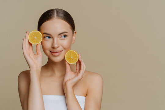 Horizontal shot of thoughtful young European woman uses homemade fruit for facial mask holds lemon slices wrapped in white soft bath towel looks aside isolated over brown background copy space