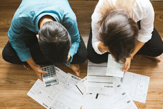 Top view asian couple sitting on the floor stressed and confused by calculate expense from invoice or bill, have no money to pay think of take the house to mortgage causing debt, bankruptcy concept.