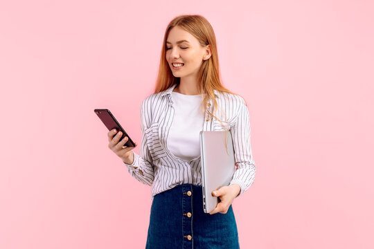 Shocked young businesswoman with laptop, uses mobile phone, on pink background