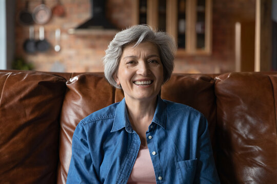 Active old age. Portrait of optimistic retired hispanic female clothed in stylish casual demonstrating perfect white teeth in beautiful smile. Energetic senior latin woman sit on couch look at camera
