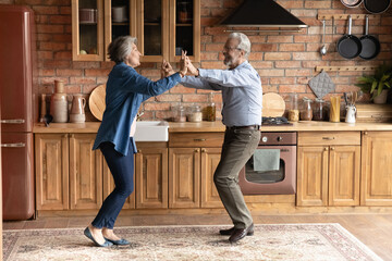 Cook with a twist. Active aged family couple enjoy cooking dancing at modern designed wooden kitchen distracted of preparing meals. Energetic older spouses have dance party for two at country cottage