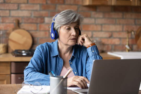 Virtual learning for aged people. Active latin female retiree sit by laptop in headset confer with teacher at remote lesson training. Mature hispanic woman take part at online event via internet app