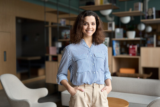 Young smiling latin girl college student or teacher looking at camera standing in university campus. Happy hispanic millennial woman professional posing in modern coworking creative office space.