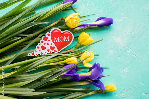 Dear greetings for Mothers Day with a bouquet of daffodils, purple irises and red heart with the text MOM ,Happy Mothers Day concept.Postcard with fresh spring flowers