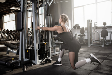 Rear view shot of a fitness woman exercising at sports studio