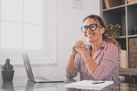 Happy young caucasian businesswoman smiling working online watching webinar podcast on laptop and learning education course conference calling make notes sit at work desk, elearning concept.