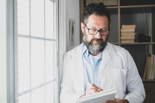 Pensive young male caucasian doctor in white medical uniform look in window distance thinking or pondering, serious man GP plan future career or success in medicine, visualize at workplace writing.