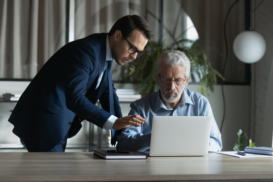 Young man CEO or boss help middle-aged colleague with computer in office. Diverse male coworkers brainstorm cooperate using laptop at workplace. Businessmen engaged in online work. Teamwork concept.