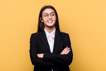 Fototapeta Young Indian business woman isolated on yellow background smiling confident with crossed arms.