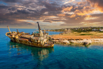 Old ship off coast of Cyprus. Abandoned ship near city of Paphos. Sights of beaches of Cyprus. Rusty ship off Mediterranean coast. Paphos city in background. Holidays in Cyprus.