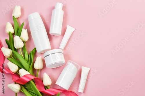 Valentines Day and Womens Day, mother's day concept. Empty white tubes and bottles with white tulips on a pink background.  Flat lay, copy space.