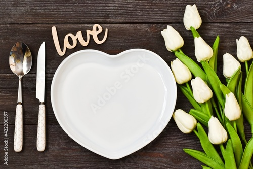 Festive creative table setting with tulip bouquet and wooden letters LOVE on wood table. Valentine's Day, Wedding Day, Birthday, Women's Day and Mother's Day. Flat lay.