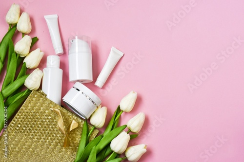 Valentines Day and Womens Day, mother's day concept. Gift bag, empty white tubes and bottles with white tulips on a pink background.  Flat lay, copy space.
