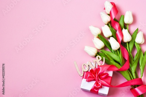 White tulips, gift box with pink ribbon on a pink background.  Flat lay, copy space. Valentines Day and Womens Day, mother's day concept. Greeting card.