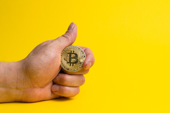 A hand holds a physical bitcoin coin. Bitcoin in hand on a yellow background. Cryptocurrency bitcoin on a yellow canvas clutching in hand.
