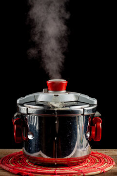 A steel pressure cooker is cooling on a fabric trivet on wooden table. The pressure valve is released and steam is coming out as the system gets depressurized. Hot steam leaving pot is seen.