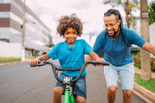 latinx father is teaching her son to ride the bike